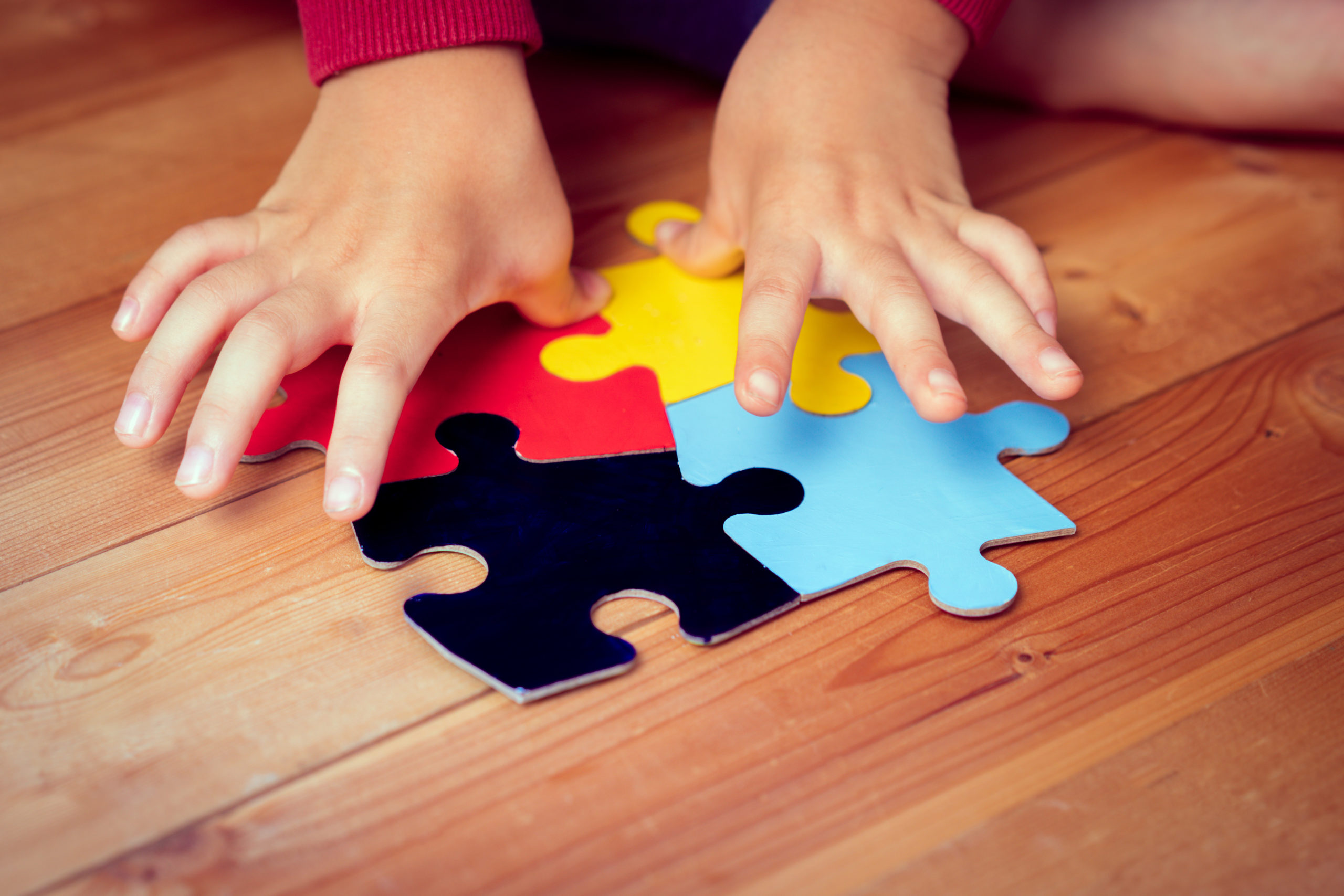 Close up: An autistic child's hands playing a puzzle symbol of Public awareness for autism spectrum disorder. World Autism Awareness day April 2, Supportive, Understanding and Acceptance. Kids health.